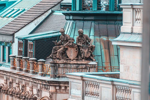 Photography of Two Person Statue Above on Building