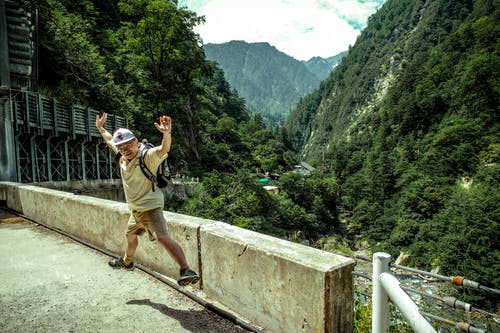 Man Jumping on Concrete Pavement Near Green Mountains Under White Sky