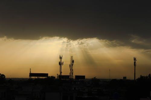 Kostenloses Stock Foto zu abendhimmel, dunkle wolken, sonnenstrahlen, stadt