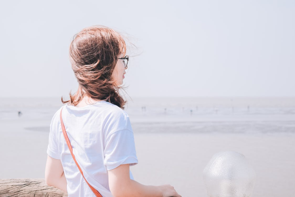 Photo of Woman in White T-shirt Overlooking the Horizon