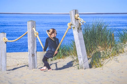 Girl Sitting On Rope At The Fence On Sand