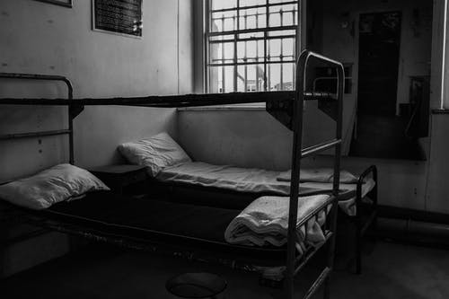 Grayscale Photography of Metal Bunk Bed and Single Bed Inside Room