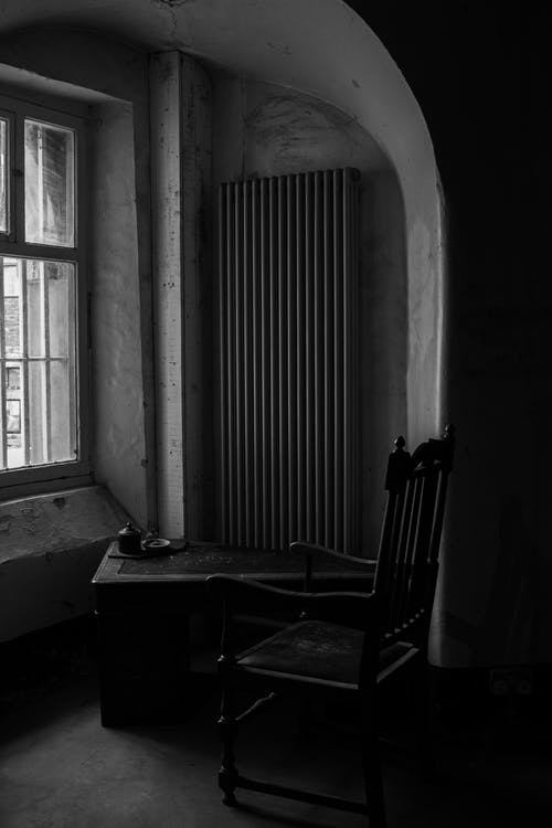 Grayscale Photography of Armchair Near Window