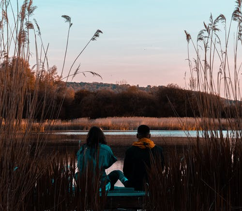 Man and Woman Sitting Near Body of Water during Golden Hour