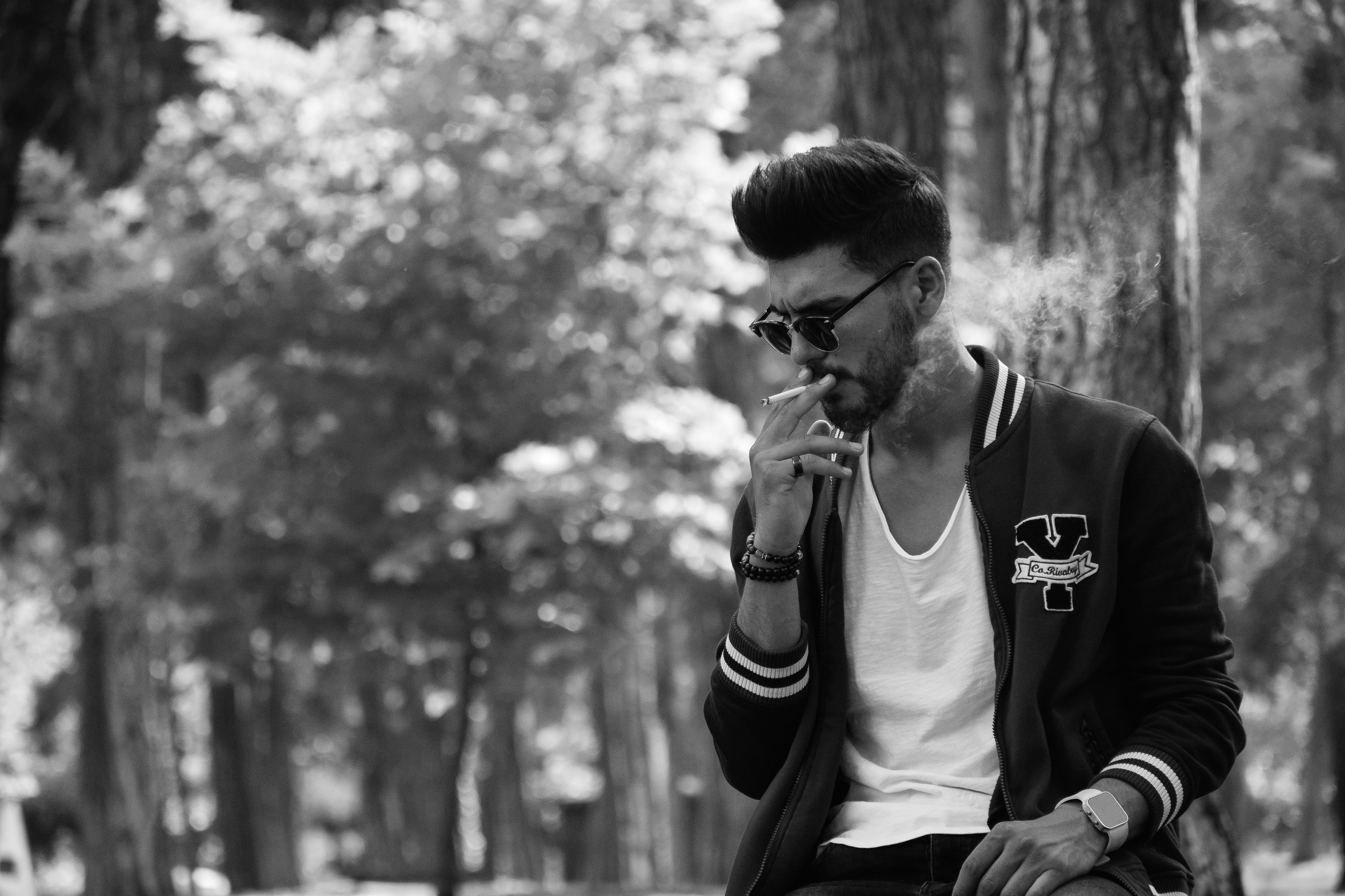 Grayscale Photo of Man in Sunglasses Smoking Cigarette
