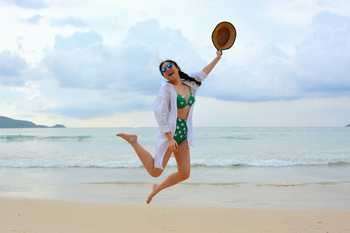 Woman Jumping on Seashore and Holding Hat