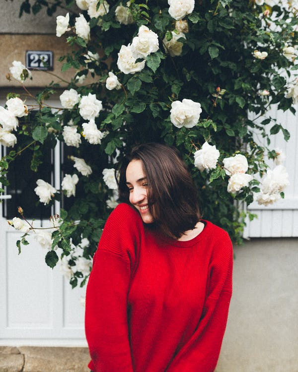 Photo of Smiling Woman in Red Long-sleeved Sweater Standing In front of White Rose Flowers