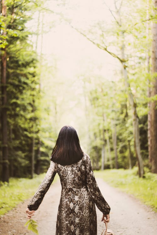 Back View Photo of Woman Walking Along Dirt Road Between Trees Carrying Bag