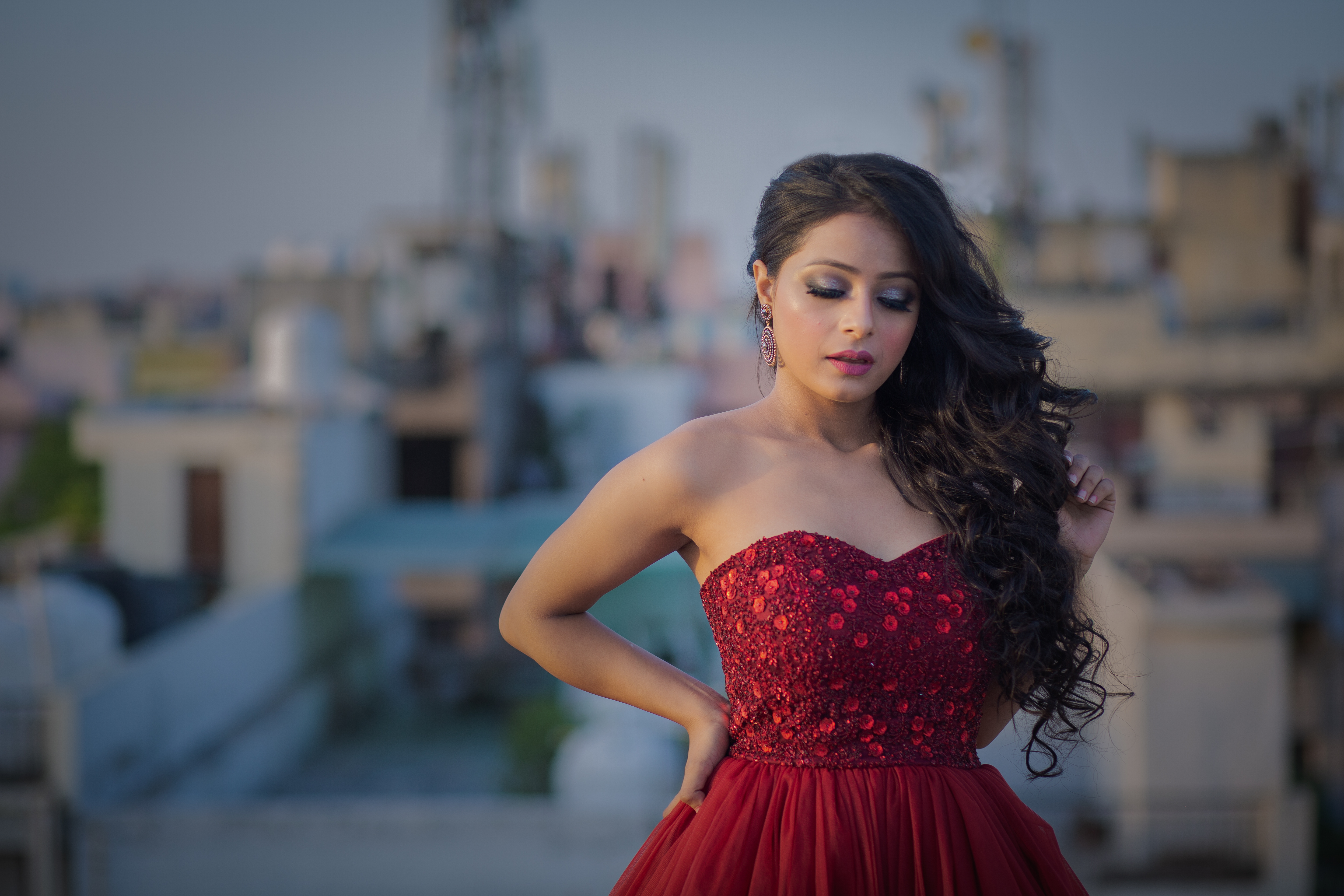 Photo of Standing Woman With Her Eyes Closed in Red Sweetheart Neckline Dress Posing