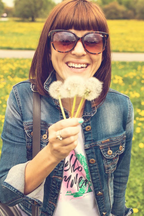 Photo of Smiling Woman in Sunglasses and Blue Denim Jacket Holding Dandelions