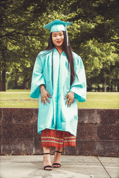 Photo of Standing Woman in Blue Academic Regalia Smiling