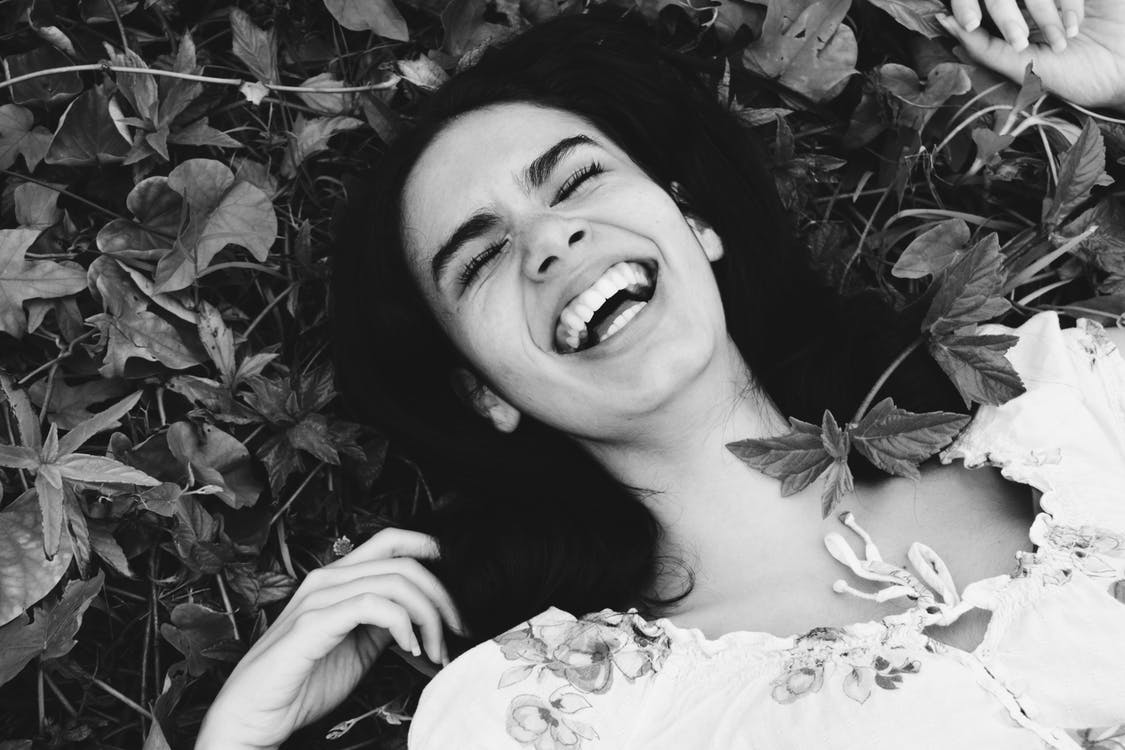 Grayscale Photo of Woman Laughing While Sleeping on Plants