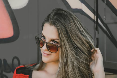 Photo of Woman Posing in Sunglasses Looking Away