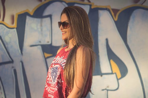 Side View Photo of Smiling Woman in Red Tank Top and Sunglasses Near Graffiti Wall