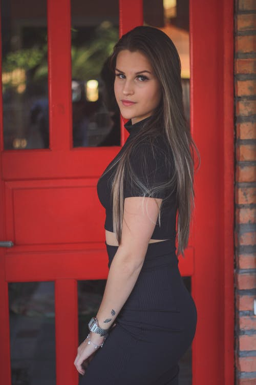 Side View Photo of Woman in Black Outfit Posing Next to Red Door