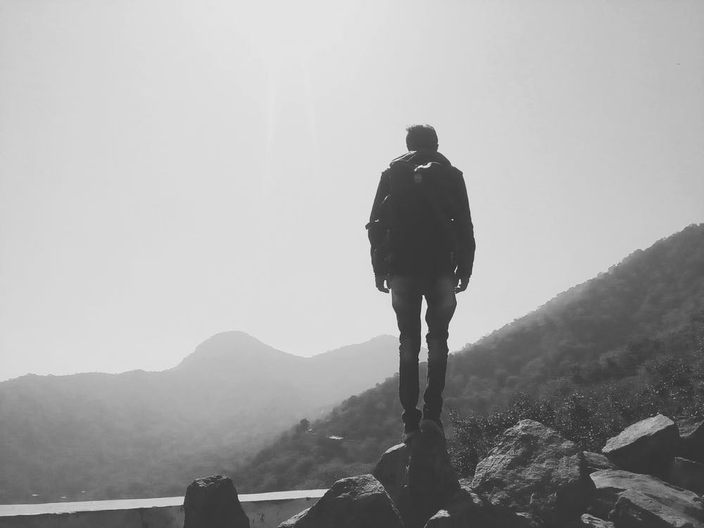 Grayscale Photo of Man Standing on a Cliff