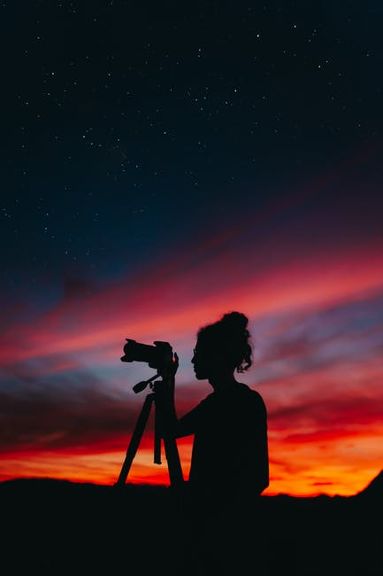 Silhouette of woman holding camera at night