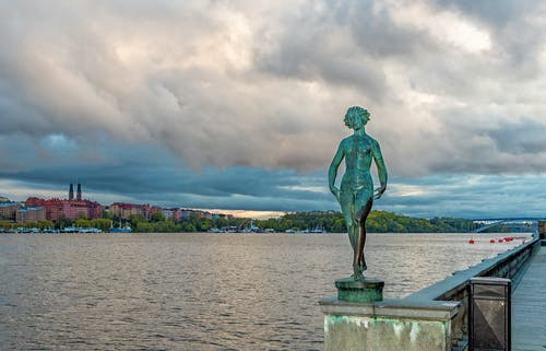 Green Statue Near Body of Water