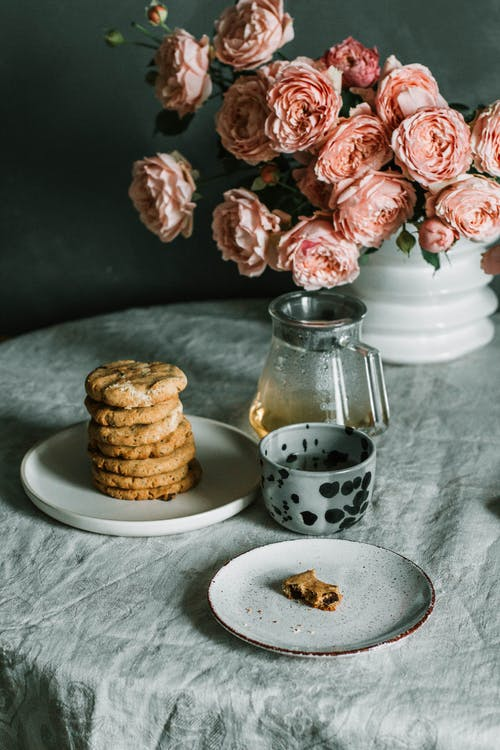Pink Flowers Beside Plate of Biscuits
