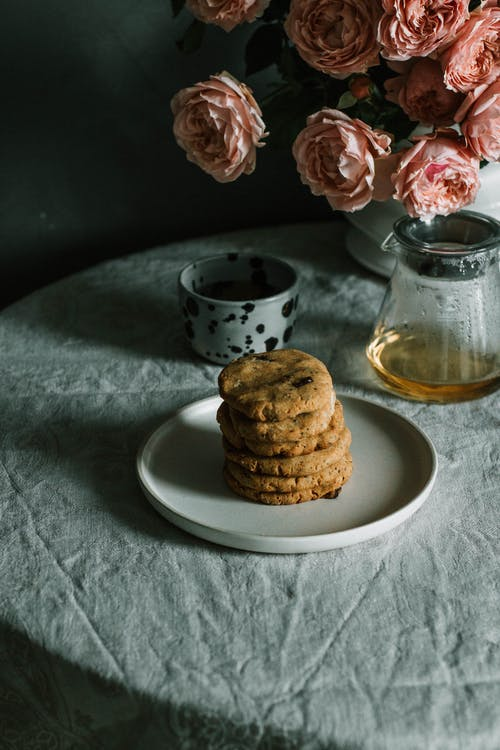 Baked Cookies on Plate Beside Teapot