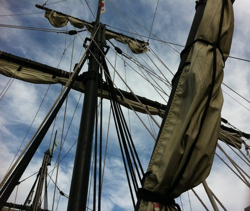 Low-angle Photography of Rolled Up Sails on Ship Under Cloudy Sky
