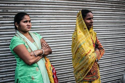 Two Women Standing Near Shutter Door