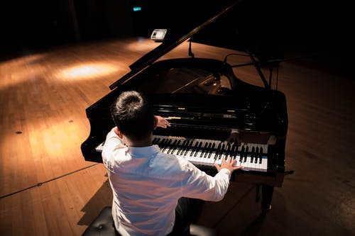 Back View Photo of a Man Playing a Black Grand Piano