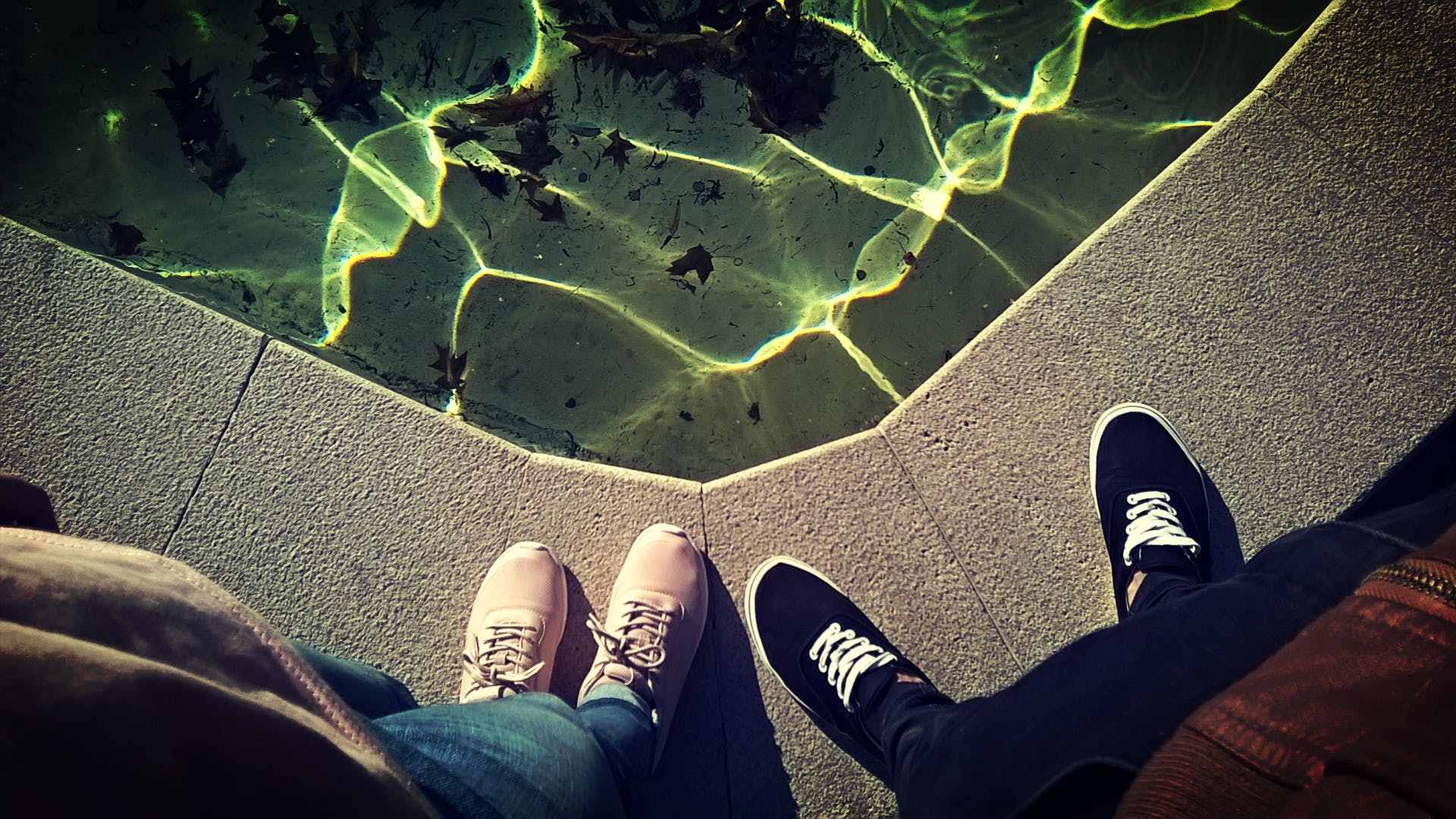 Two Person Standing Near Body of Water Taking Picture of Shoes