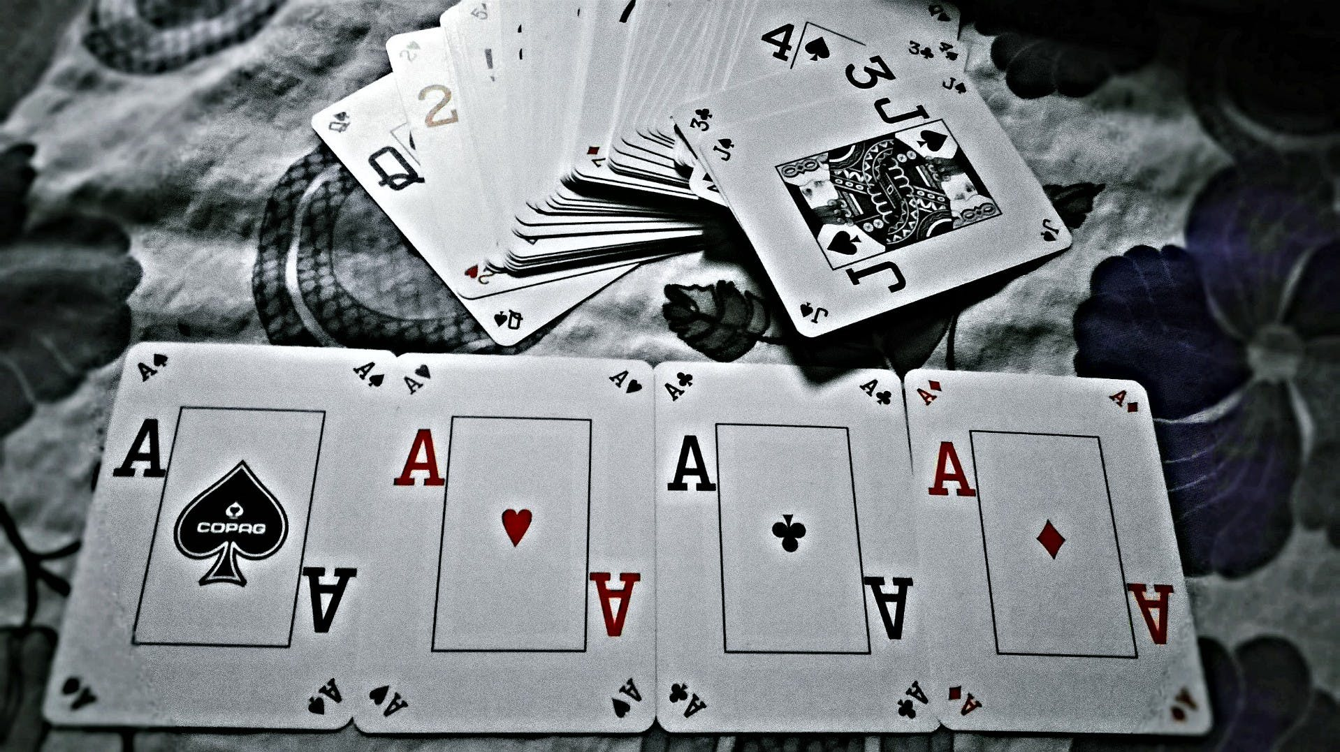Grayscale Photography of Playing Cards Placed on Cloth