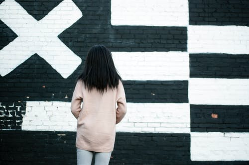 Back View Photo of Woman Standing in Front of White and Black Painted Wall