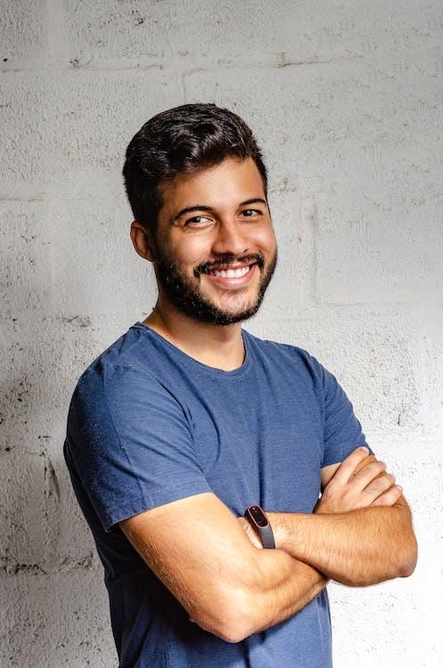 Zdjęcie Portretowe Uśmiechnięty Mężczyzna Z Rękami Skrzyżowanymi Stojąc Przed Białą ścianą