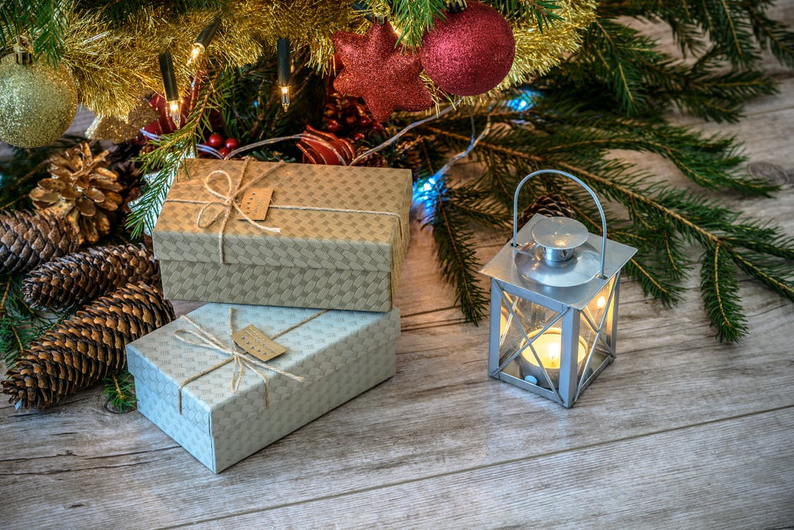 Lit Candle Inside Lantern Beside Gift Boxes and Christmas Tree