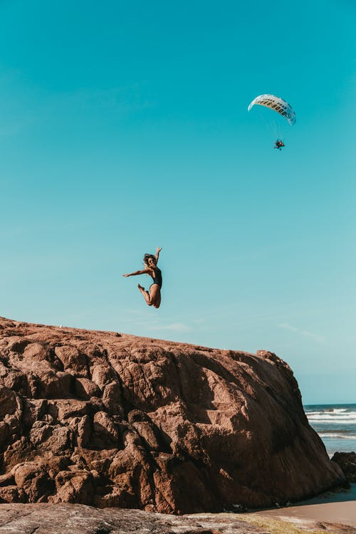 Woman Jumping on Brown Rock Formation