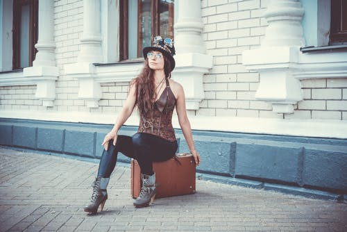 Photo of Woman Sitting on Brown Suitcase In Front of a Building