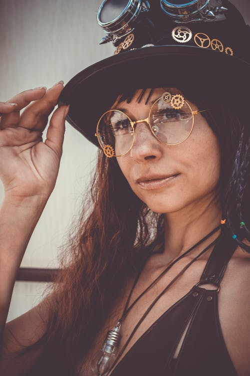 Close-up Portrait Photo of Woman In Eyeglasses Tipping Black Top Hat