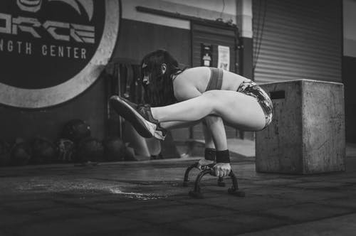 Greyscale Photo of Woman Working Out