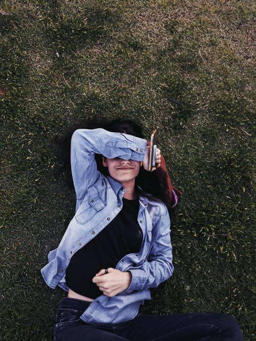 Woman Wearing Blue Denim Jacket Lying on Green Grass