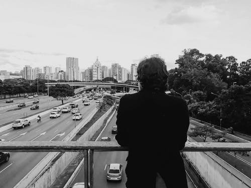 Grayscale Photo of Person on Overpass Looking at Cars