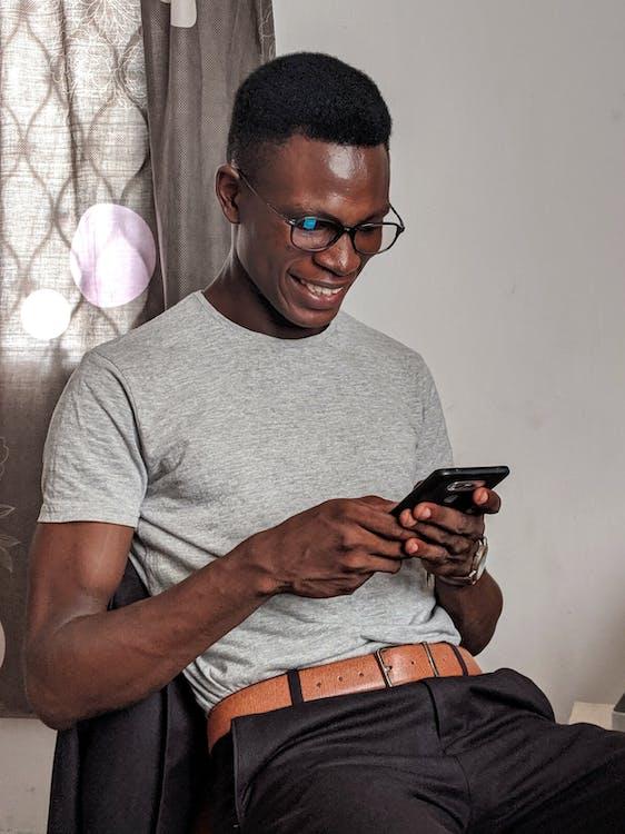 Man Wearing Gray Crew-neck Shirt Holding Black Smartphone