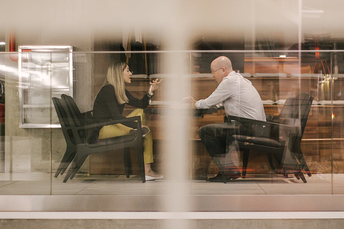 Man and Woman Sitting on Black Wooden Chairs