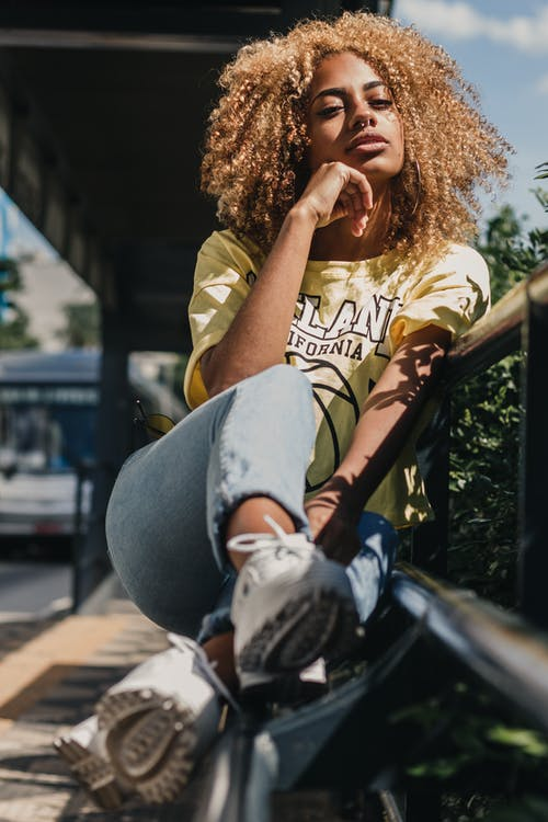 Photo of Woman in Yellow T-shirt and Blue Denim Jeans Sitting on Bench