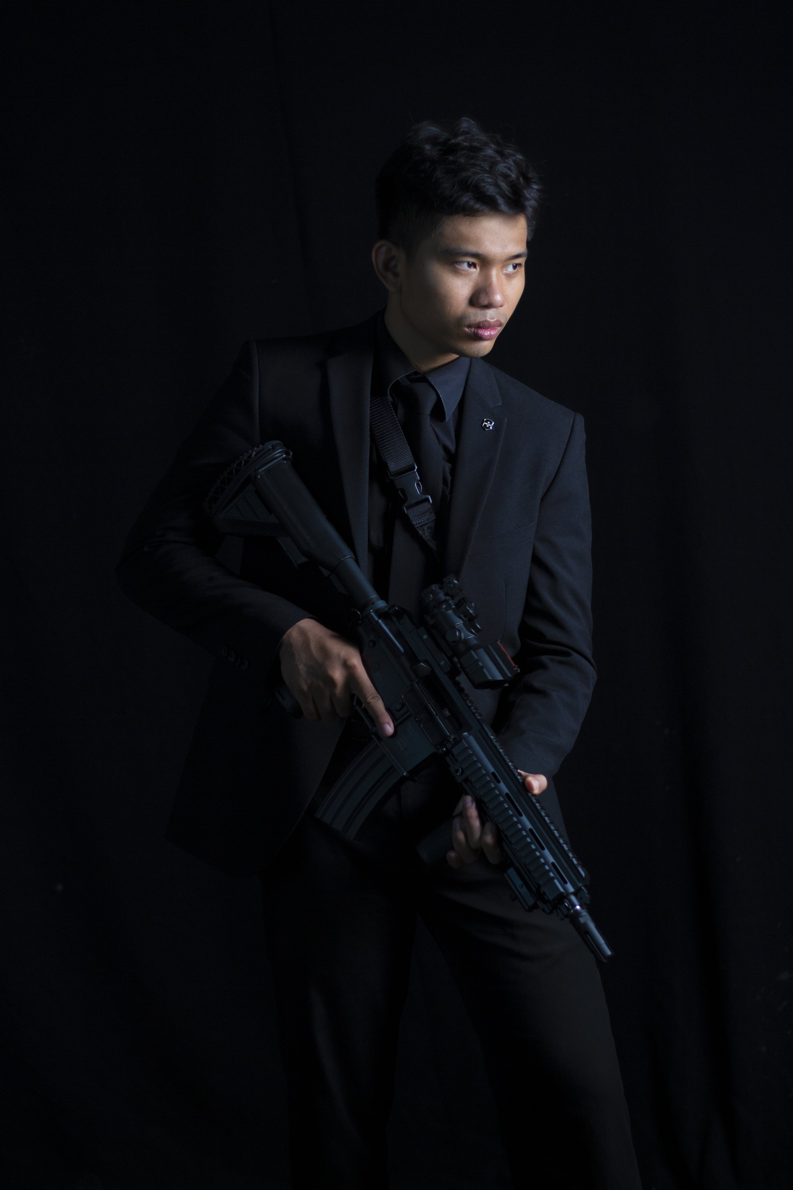 Man Wearing Black Suit and Carrying M4 Carbine With Scope