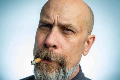 Close Up Photography of a Bearded Man with a Cigarette in His Mouth