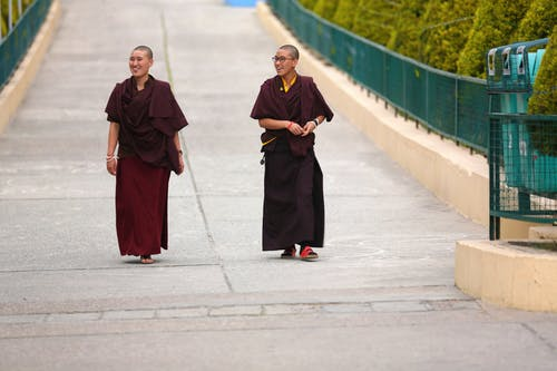 Photo of Two Monks Walking on Street