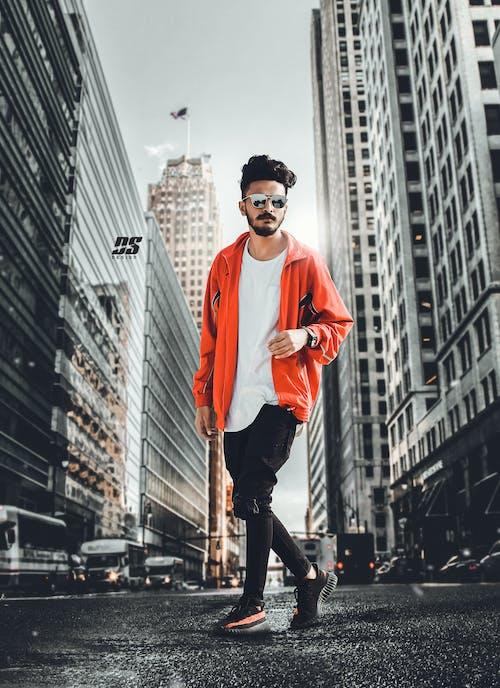 Man In Orange Jacket Standing On Street In Between High Rise Buildings