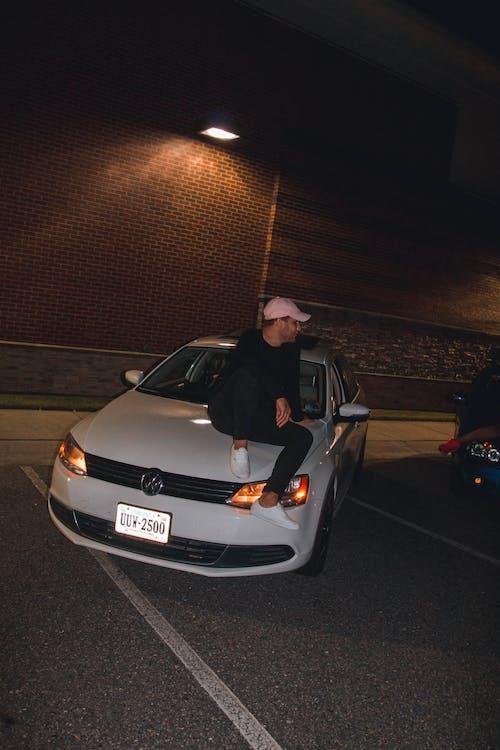 Man Sitting On Car Hood