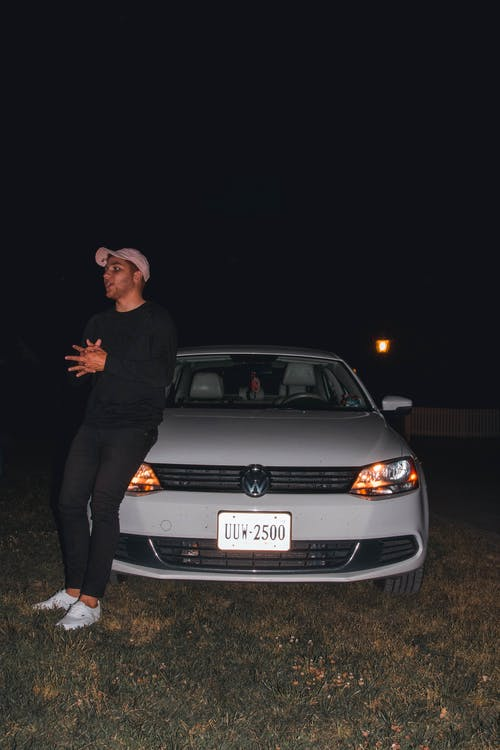 Man Leaning On White Volkswagen Vehicle At Night