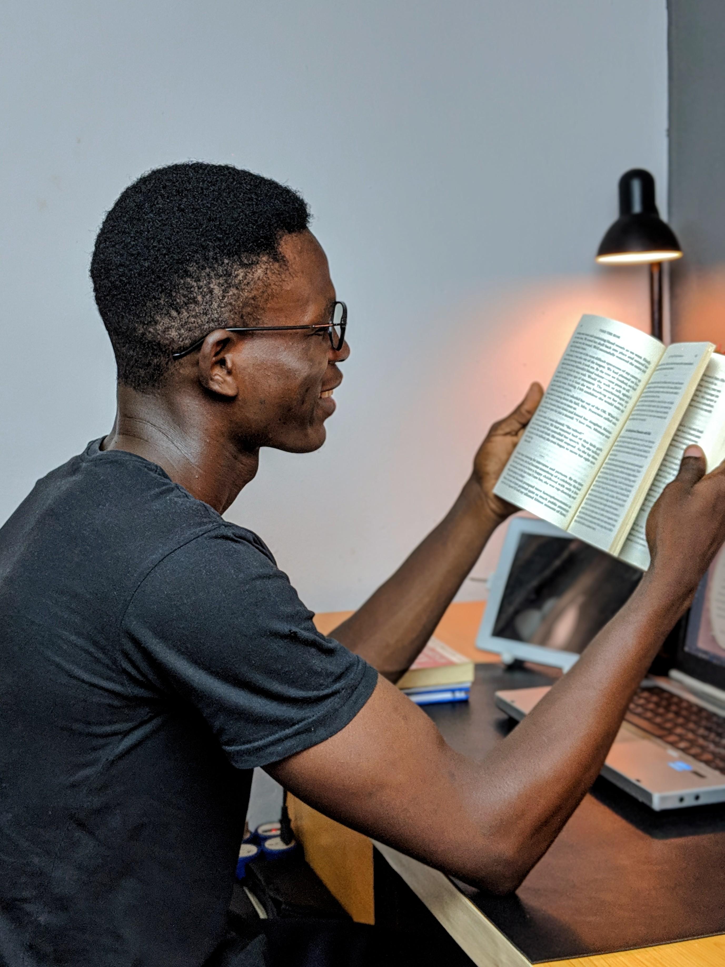 Man Wearing Gray Crew-neck Shirt Holding Book