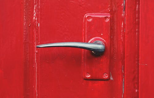 Metal door handle on a red door