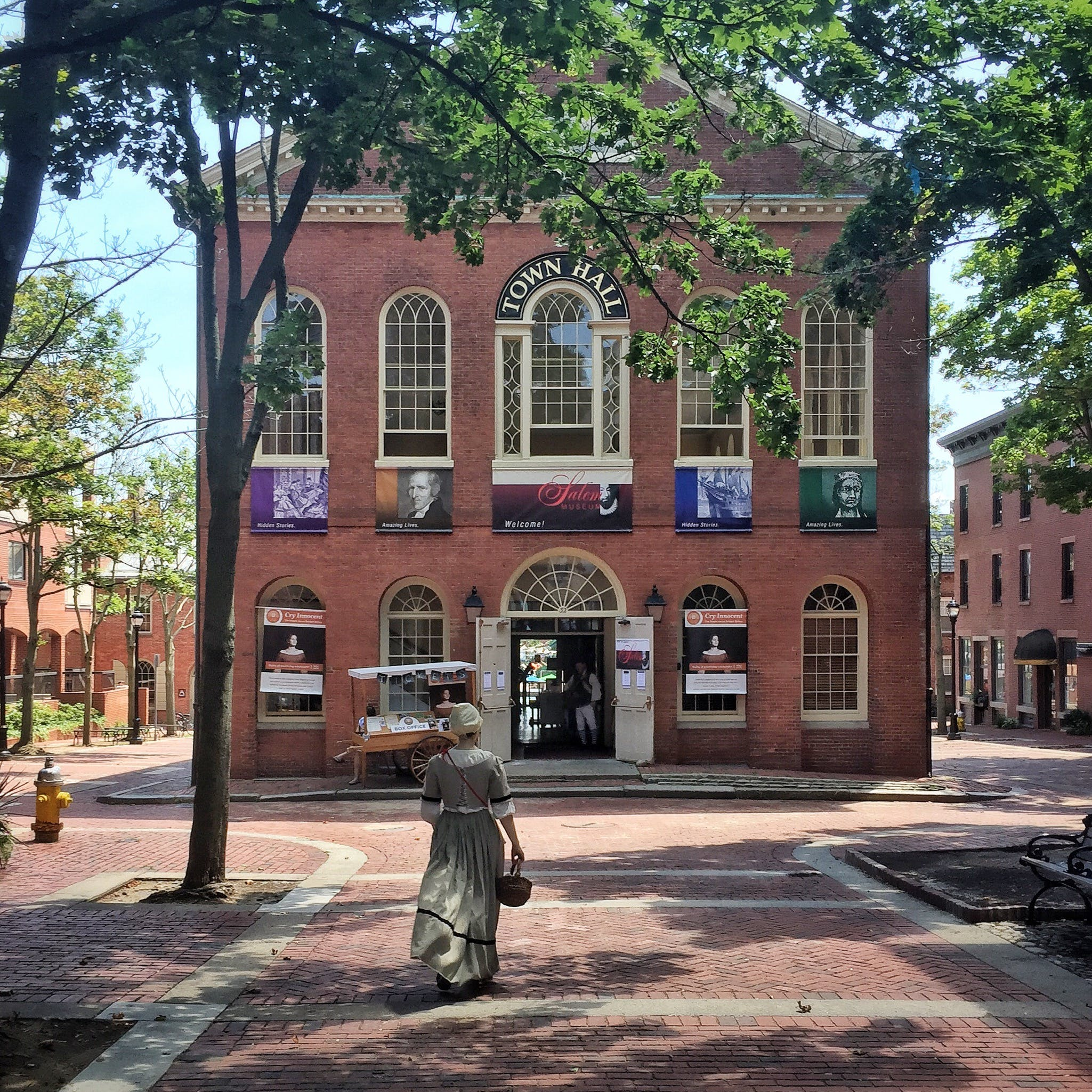 Woman Walking Through Brown Brick Town Hall
